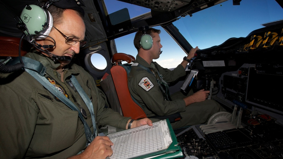 In this Monday, March 24, 2014 photo, co-pilot, Flying Officer Marc Smith turns his RAAF AP-3C Orion aircraft at low level in bad weather whilst searching for missing Malaysia Airways Flight MH370 over the Indian Ocean. (AP / Richard Wainwright)