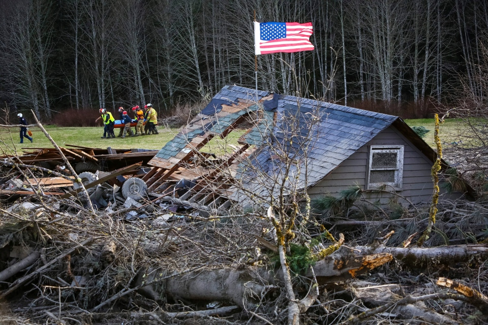 Rescue workers remove a body from the wreckage of homes destroyed by a mudslide near Oso, Wash., Monday, March 24, 2014. (Seattlepi.com / Joshua Trujillo)