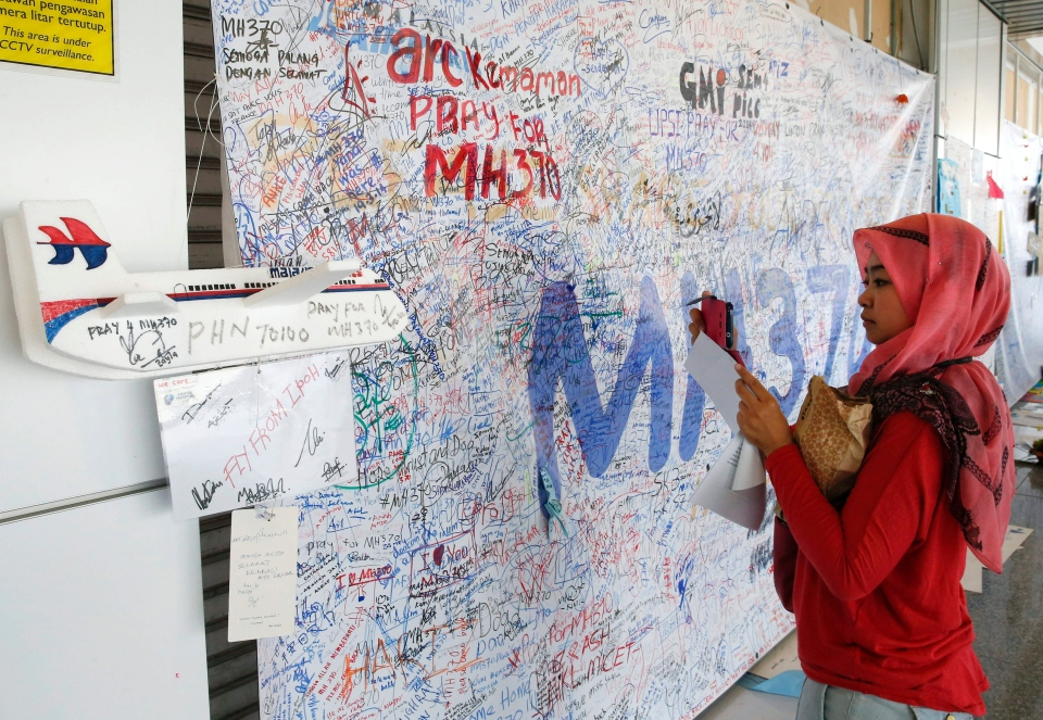A Malaysian woman takes a picture of a message board for passengers aboard the missing Malaysia Airlines plane at Kuala Lumpur International Airport in Sepang, Malaysia on Wednesday, March 25, 2014. (AP / Vincent Thian)