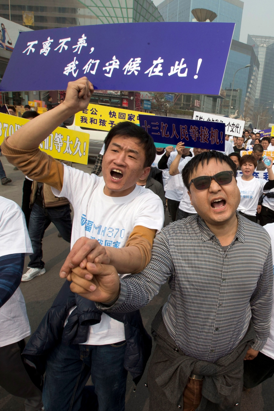 Relatives of Chinese passengers onboard the Malaysia Airlines plane, MH370, protest with placards one of which reads 'We won't leave or ditch you, we will wait right here' as they march towards the Malaysian embassy in Beijing, China on Wednesday, March 25, 2014. (AP / Ng Han Guan)