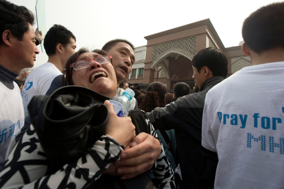 A relative of Chinese passengers on board a missing Malaysia Airlines plane breaks down as she protests outside the Malaysia Embassy in Beijing, China, Tuesday, March 25, 2014. (AP / Ng Han Guan)