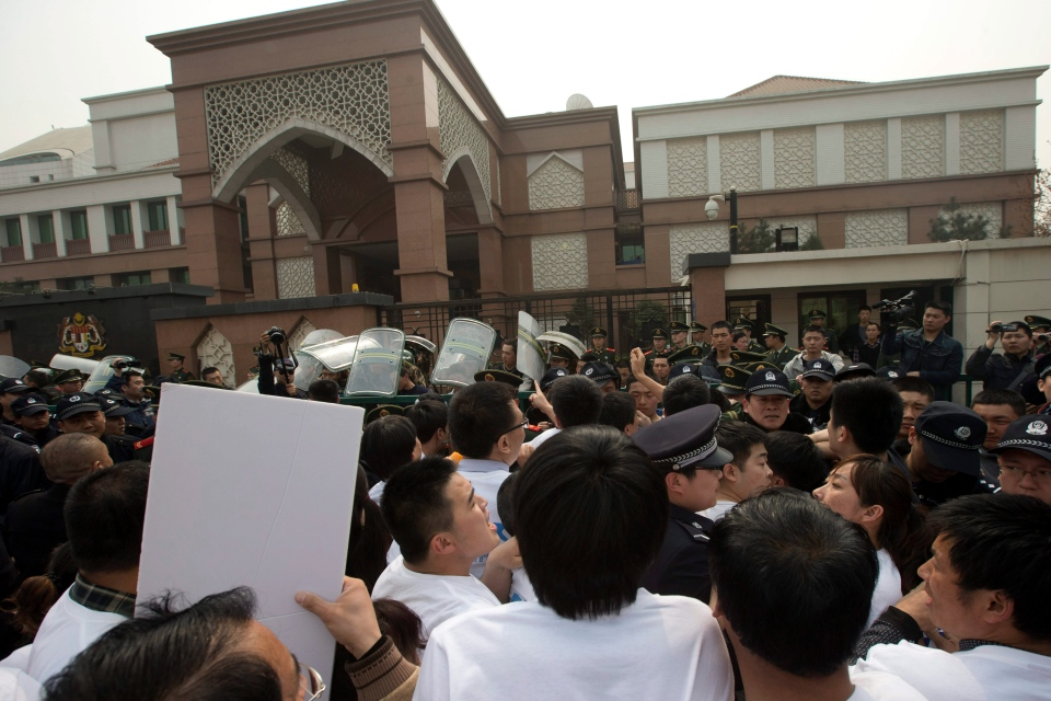 Chinese relatives of Chinese passengers onboard the missing Malaysia Airlines plane, flight MH370, scuffle with police officers outside the Malaysia embassy in Beijing, China, Tuesday, March 25, 2014. (AP / Ng Han Guan)
