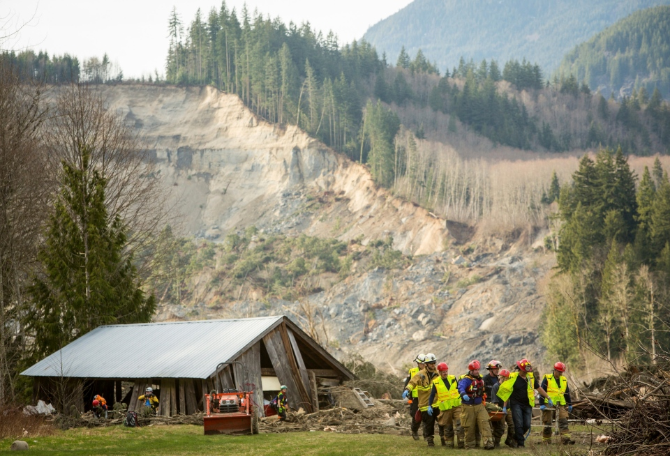 Rescue workers remove one of a number of bodies from the wreckage of homes destroyed by a mudslide near Oso, Wash, Monday, March 24, 2014. (seattlepi.com / Joshua Trujillo)