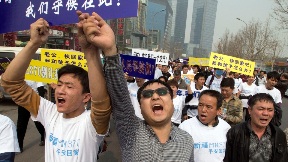 Chinese relatives of passengers onboard the missing Malaysia Airlines plane, flight MH370, shout in protest as they march towards the Malaysia embassy in Beijing, China, Tuesday, March 25, 2014. (AP / Ng Han Guan)