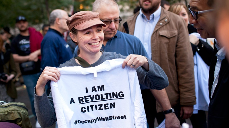 Cate Nolan, from Brooklyn, New York, holds up a shirt that says