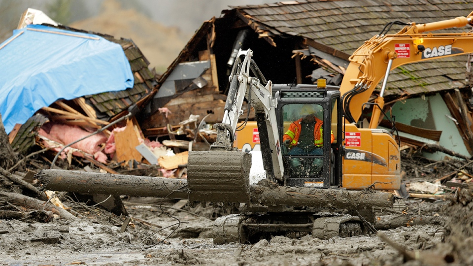 Workers using heavy equipment work to clear debris near a destroyed house that came to rest on Washington Highway 530 on the western edge of the massive mudslide that struck near Arlington, Wash., Tuesday, March 25, 2014. (AP / Ted S. Warren)