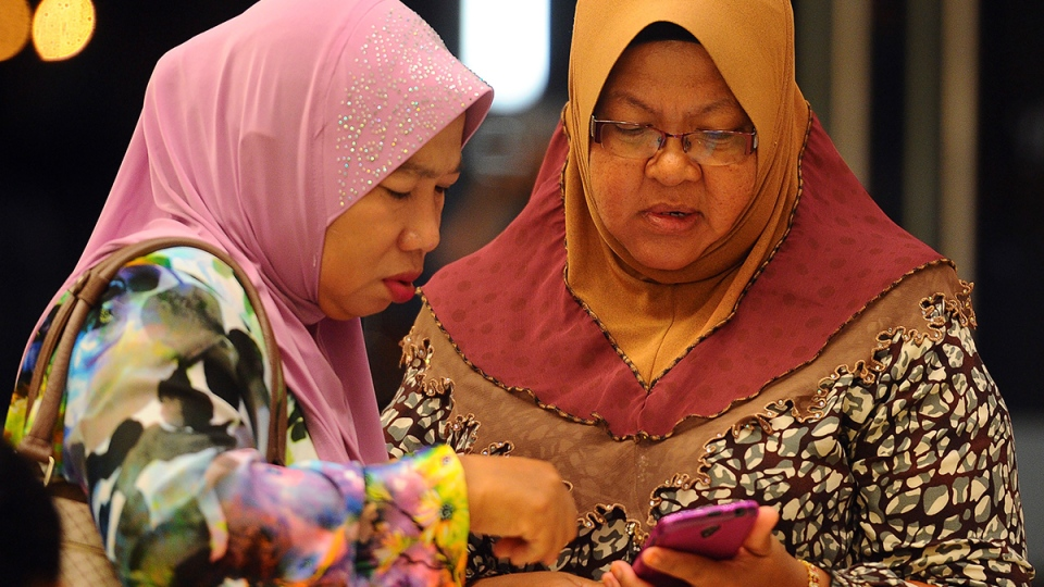 Family members of passengers aboard a missing Malaysia Airlines plane check a mobile phone before a briefing at a hotel in Putrajaya, Malaysia, Tuesday, March 25, 2014. (AP / Joshua Paul)