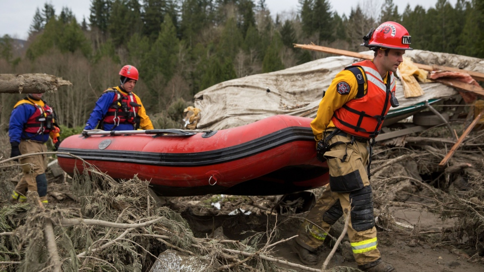 Rescue workers carry an inflatable boat to the flooded area in the debris field caused by the massive mudslide above the North Fork of the Stillaguamish River onto Highway 530, as recovery efforts continue, near Oso, Wash., on Tuesday, March 25, 2014. (The Seattle Times / Marcus Yam)