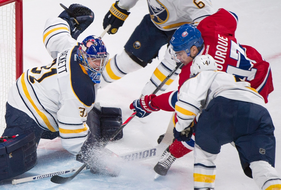 Buffalo Sabres' goaltender Matt Hackett, left, makes a save against Montreal Canadiens' Rene Bourque (17) as Sabres' Jamie McBain defends during first period NHL hockey action in Montreal, Tuesday, March 25, 2014. THE CANADIAN PRESS/Graham Hughes
