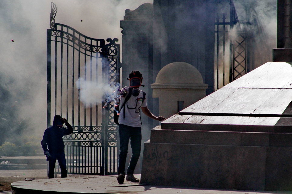 A protester fires a flare during clashes with security forces outside of Cairo University in Giza, Egypt, Wednesday, March 26, 2014. (AP /Ahmed Abd El Latif, El Shorouk)