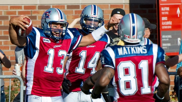 Montreal Alouettes quarterback Anthony Calvillo celebrates after scoring a touchdown against the Toronto Argonauts with teammates Brandon London, rear, and Kerry Watkins, right, during third quarter CFL football action in Montreal on Monday, October 10, 2011. (Paul Chiasson / THE CANADIAN PRESS)