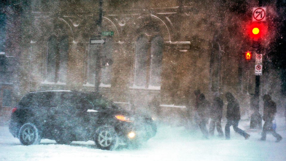 Pedestrians battle high winds and blowing snow as they walk in downtown Halifax on Wednesday, March 26, 2014. (Andrew Vaughan / THE CANADIAN PRESS)