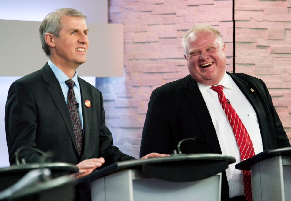 Mayor Rob Ford, right, laughs next to David Soknacki during a commercial break as they take part in a live television mayoral debate in Toronto on Wednesday, March 26, 2014. (Nathan Denette / THE CANADIAN PRESS)