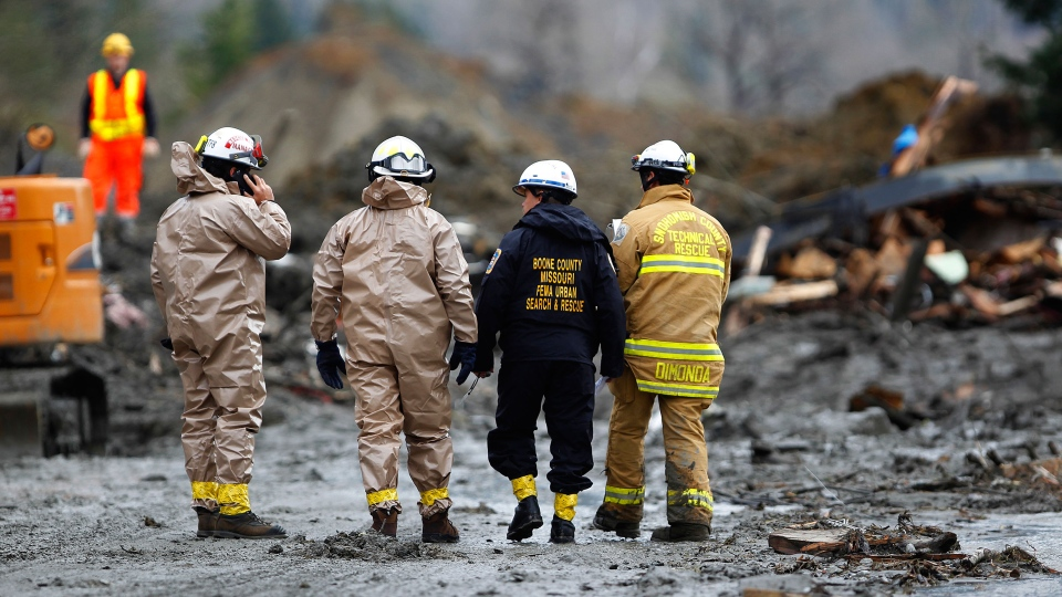 Rescue workers and work crews toil at the western edge of the mudslide where it covers Highway 530 east of Oso, Wash. Wednesday, March 26, 2013. (The Herald / Mark Mulligan)
