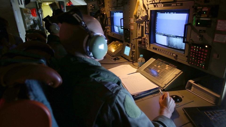 Crew members keep watch on the radar on board a Royal Australian Air Force AP-3C Orion during a search for the missing Malaysia Airlines Flight 370 in the southern Indian Ocean, Wednesday, March 26, 2014. (AP / Paul Kane)