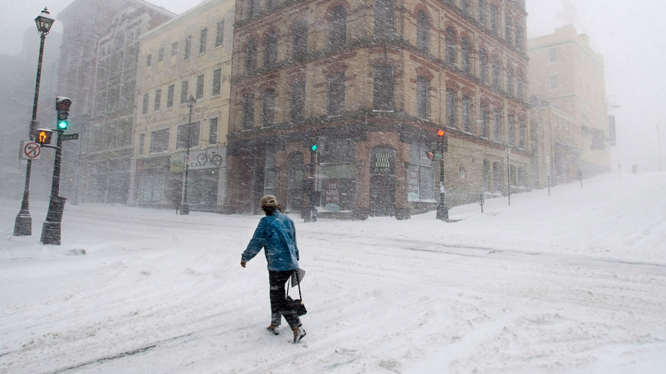 A person walks through a spring snow storm in Halifax Wednesday, March 26, 2014. (Andrew Vaughan / THE CANADIAN PRESS/Andrew Vaughan)