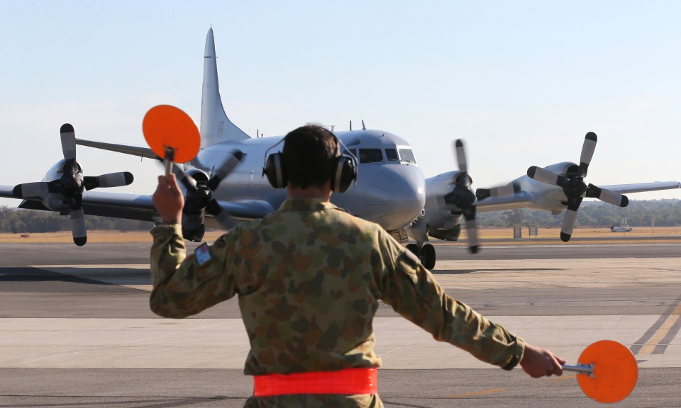 Royal Australian Air Force AP-3C Orion is guided by a ground crew man on the tarmac at RAAF Base Pearce following their search operation for the missing Malaysia Airlines Flight MH370 in Perth, Australia, Thursday, March 27, 2014. (AP / Rob Griffith)