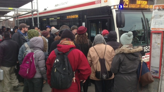 Passengers attempt to board a 29 Dufferin bus at Dufferin and Bloor streets Thursday, March 27, 2014. (Cam Woolley/CP24)