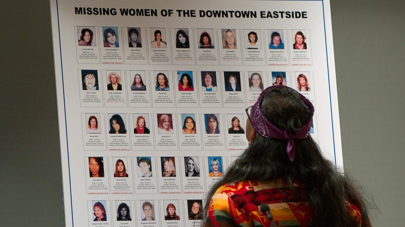 Elder Eugene Harry of the Squamish Nation looks at a poster of missing women prior to performing a ceremonial blessing at the start of the missing women inquiry in downtown Vancouver, Tuesday, Oct. 11, 2011.  (Jonathan Hayward / THE CANADIAN PRESS)