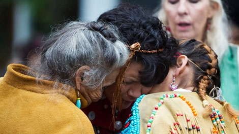 Cee Jai Julian, centre, embraces two women outside the missing women inquiry in downtown Vancouver, Tuesday, Oct. 11, 2011. Commissioner Wally Oppal has opened hearings to examine why police failed to stop Robert Pickton as he murdered impoverished sex workers from Vancouver's Downtown Eastside.THE CANADIAN PRESS/Jonathan Hayward