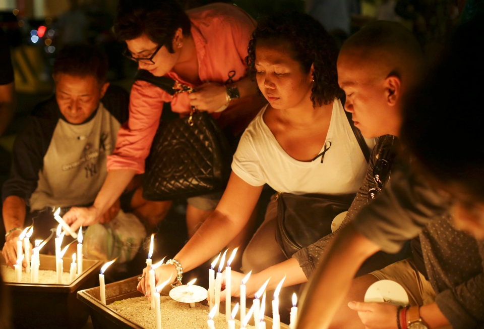 People place candles during a ceremony in memory of passengers on board the missing Malaysia Airlines Flight MH370 in Kuala Lumpur, Malaysia on Thursday, March 27, 2014. (AP / Aaron Favila)