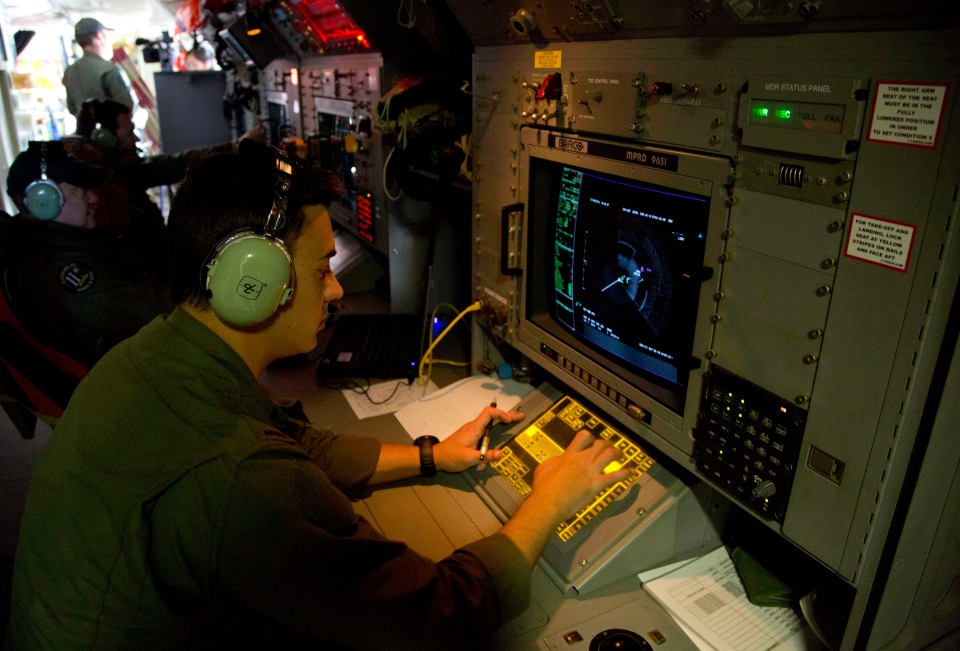 gt. Matthew Falanga, an airborne electronics analyst, observes a radar image aboard a Royal Australian Air Force AP-3C Orion aircraft during a search operation of the missing Malaysian Airlines Flight 370 over the southern Indian Ocean on Thursday, March 27, 2014. The disappearance of the airplane has presented two tales of modern technology. The public has been surprised to learn of the limitations of tracking and communications devices. (AP Photo/Michael Martina, Pool, File)