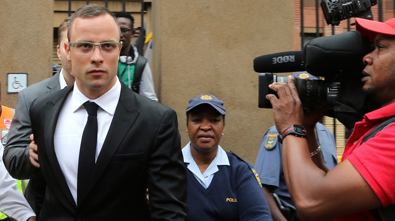 Oscar Pistorius, left, leaves the high court in Pretoria, South Africa, Friday, March 28, 2014. (AP / Themba Hadebe)