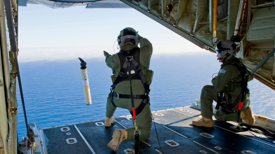 Royal Australian Air Force Loadmasters Sgt. Adam Roberts, left, and Flight Sgt. John Mancey, launch a Self Locating Data Marker Buoy from a C-130J Hercules aircraft in the southern Indian Ocean as part of the Australian Defence Force's assistance to the search for Malaysia Airlines flight MH370, March 20, 2014. (AP / Australian Defence Department, Justin Brown, File)