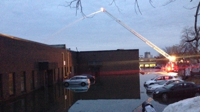Firefighters pour water on a Fairbank Avenue industrial building in Toronto early Friday, March 28, 2014. (Cam Woolley / CP24)