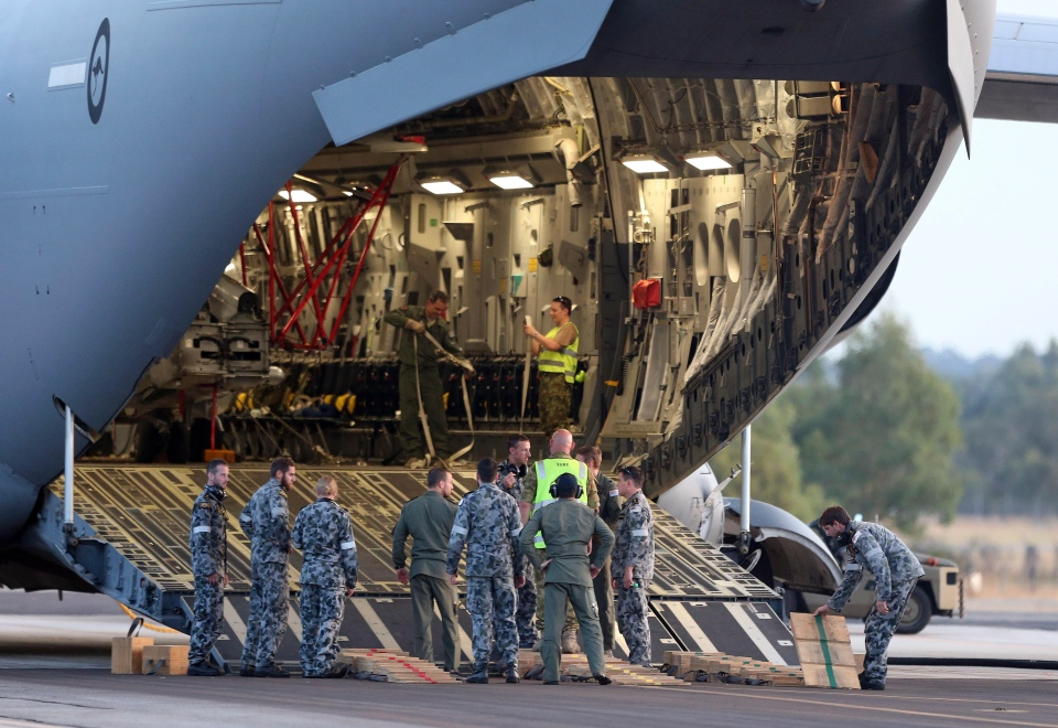 Ground crew prepare to unload a Sea Hawk helicopter from a Royal Australia Air Force C-17 after it landed at RAAF Base Pearce to help with the search for the missing Malaysia Airlines Flight MH370 in Perth, Australia, Friday, March 28, 2014.  (AP / Rob Griffith)