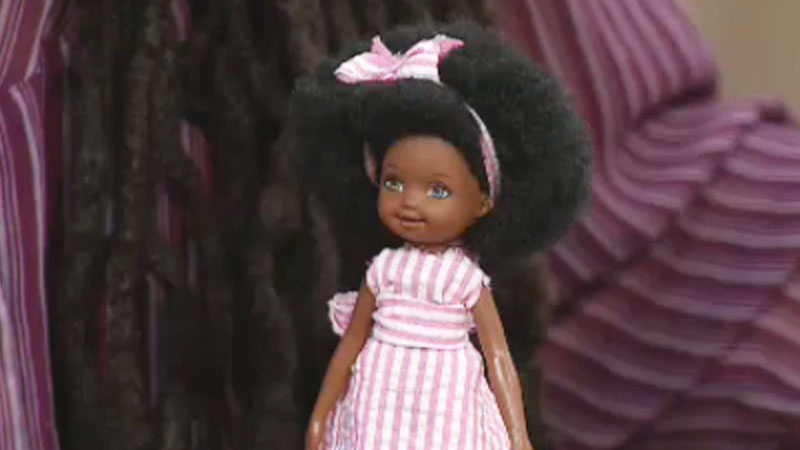 Queen Cee holds a doll that she styled to look like her daughter.