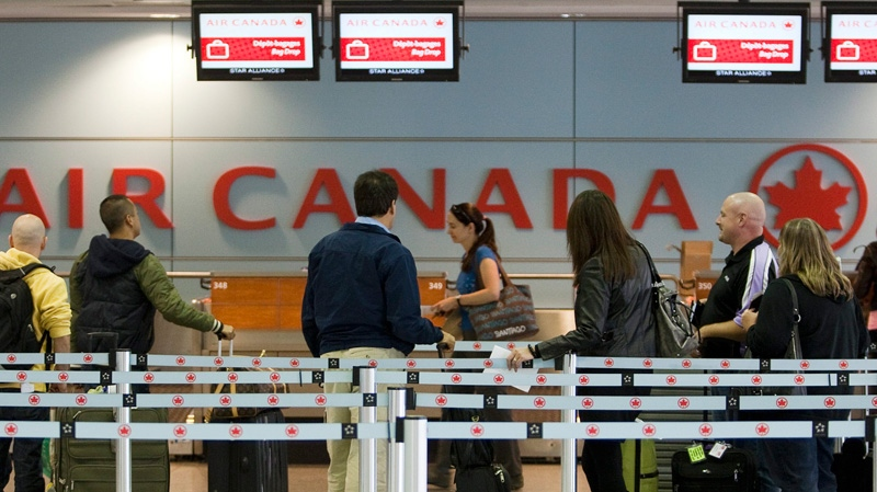 Air Canada passengers wait to check-in at Pierre Elliott Trudeau Airport in Montreal on Wednesday, Oct. 12, 2011.  (Ryan Remiorz / THE CANADIAN PRESS)