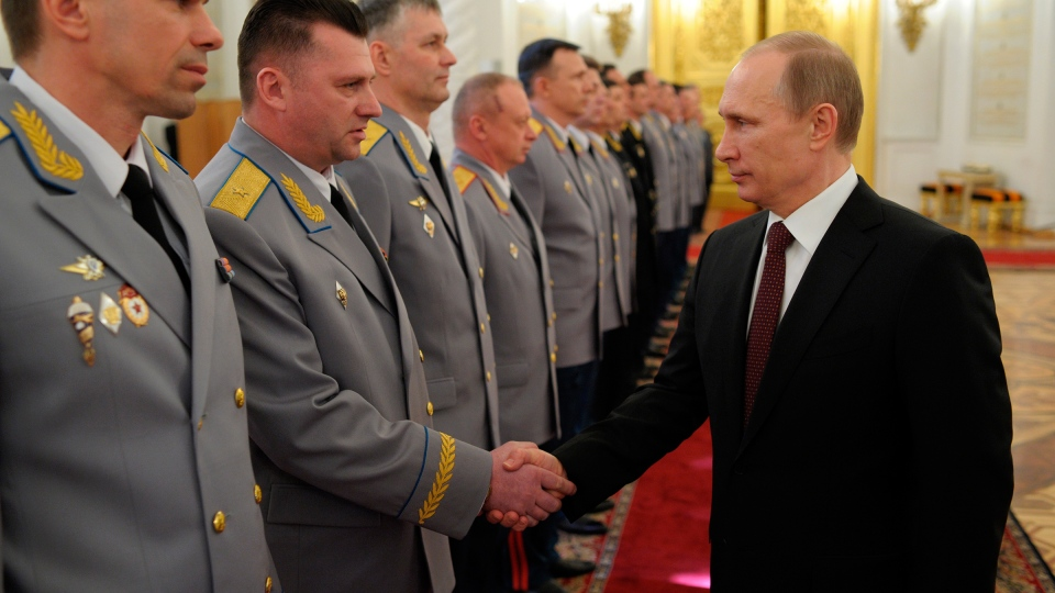 Russian President Vladimir Putin, right, shakes hands at the presentation ceremony of the top military brass in the Kremlin in Moscow, Russia, Friday, March 28, 2014. (RIA-Novosti / Alexei Druzhinin, Presidential Press Service)