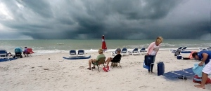 As a fast-moving line of storm clouds approaches from the gulf, beach goers pack up ahead of the rain on Pass-a-Grille Beach about Tuesday afternoon, Jan. 21, 2014 in St. Petersburg Fla. (The Tampa Bay Times / Cherie Diez)