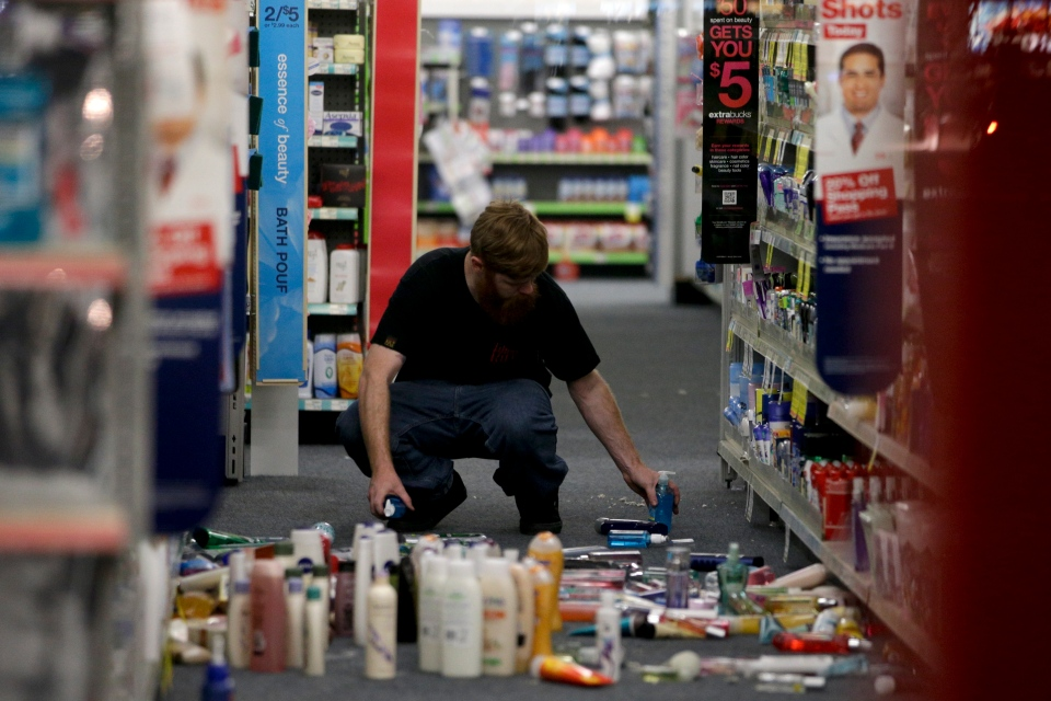 A man picks up fallen goods at a CVS store after an earthquake on March 28, 2014, in La Mirada, Calif. A magnitude-5.1 earthquake was widely felt in the Los Angeles area and surrounding counties Friday evening, but authorities said there were no immediate reports of significant damages or injuries. (AP Photo/Jae C. Hong)