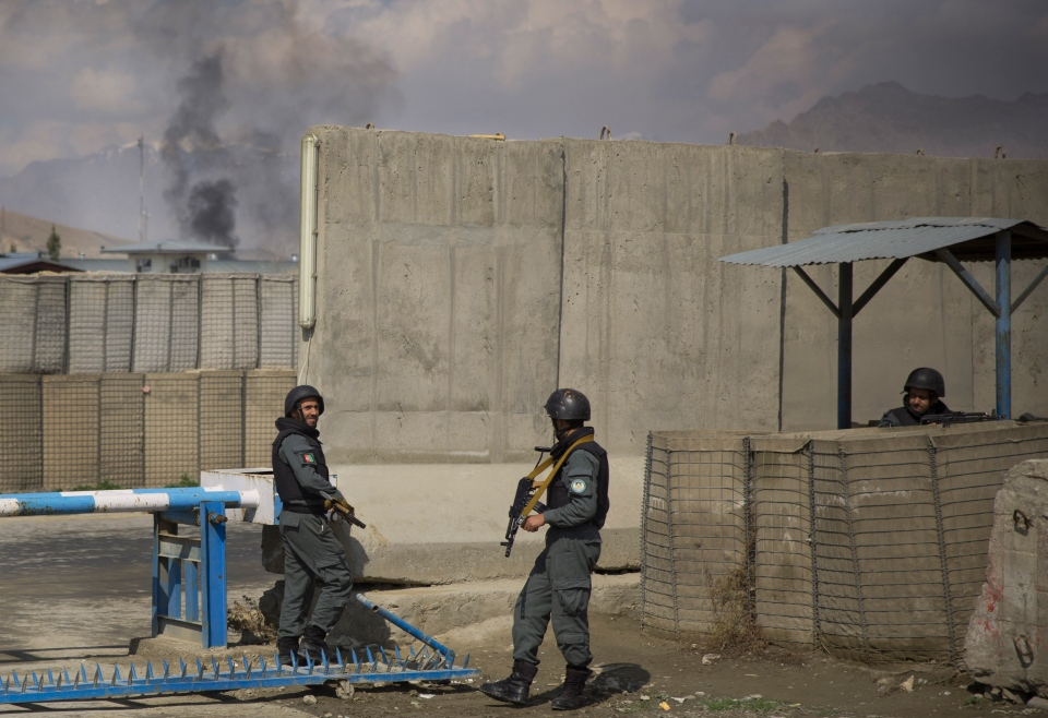 Afghan policemen take position while smoke from a burning building billows in the background as Taliban militants attacked the main Afghan election commission's headquarters in the outskirts of Kabul, firing on the compound with rocket-propelled grenades and heavy machine guns from a house outside its perimeter wall on March 29, 2014. (AP / Anja Niedringhaus)