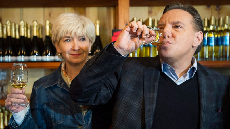 Coalition Avenir Quebec Leader Francois Legault and wife Isabelle Blais try a glass of cider during a Quebec provincial election campaign stop at an apple orchard and cidery in Mont-St-Gregoire, Que., Saturday, March 29, 2014. THE CANADIAN PRESS/Graham Hughes