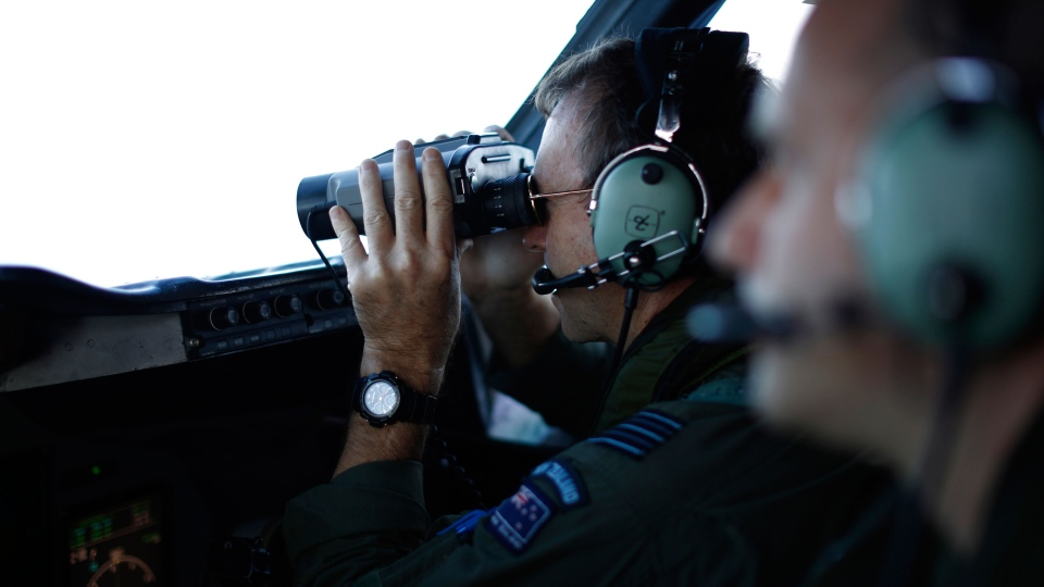 Wing Commander Rob Shearer looks through binoculars on the flight deck of a Royal New Zealand Air Force P-3K2 Orion aircraft searching for missing Malaysian Airlines flight 370 over the southern Indian Ocean, March 29, 2014. (AP / Jason Reed, Pool)