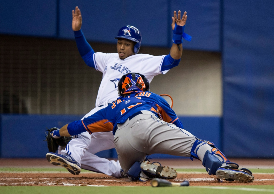 Toronto Blue Jays' Moises Sierra is tagged out at home by New York Mets' Travis d'Arnaud to end the third inning during a pre-season game Saturday, March 29, 2014 in Montreal. (Paul Chiasson / THE CANADIAN PRESS)