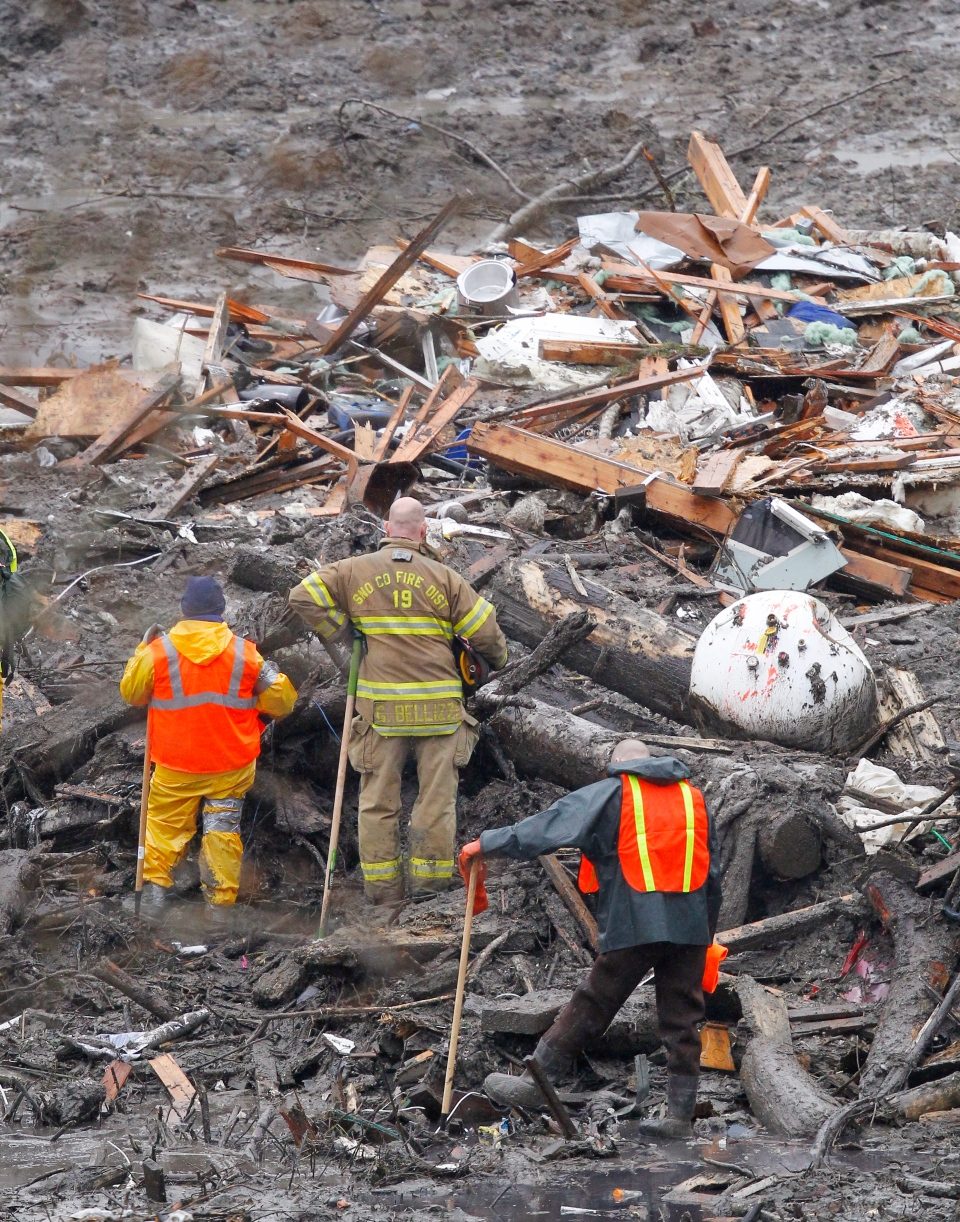 Searchers pause for a moment of silence at the scene of a deadly mudslide Saturday, March 29, 2014, in Oso, Wash. Besides the more than two dozen bodies already found, many more people could be buried in the debris pile left from the mudslide one week ago. Ninety people are listed as missing. (AP / Elaine Thompson, Pool)