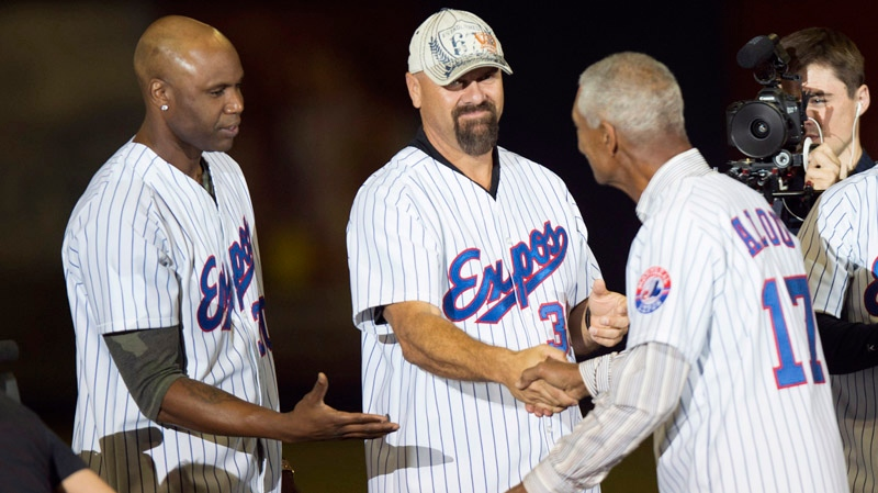 Former Montreal Expos manager Felipe Alou shakes hands with Larry Walker and Cliff Floyd, left, as members of the 1994 Expos are introduced prior to a pre-season game with the Toronto Blue Jays facing the New York Mets Saturday, March 29, 2014 in Montreal. THE CANADIAN PRESS/Paul Chiasson