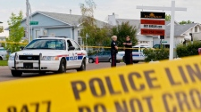 Police investigate a murder at a home in Edmonton on July 10, 2010. (John Ulan / THE CANADIAN PRESS)