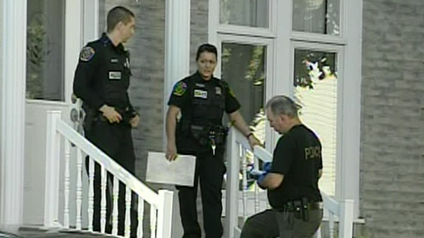 Police officers at the scene of a St. Eustache home where a woman allegedly attempted to kill her children (Oct. 10, 2011)
