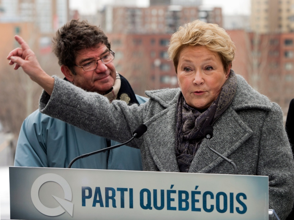 Parti Quebecois leader Pauline Marois speaks to the media as PQ candidate Pierre Paquette looks on while campaigning Saturday, March 29, 2014 in Montreal, Que. (Ryan Remiorz / THE CANADIAN PRESS)