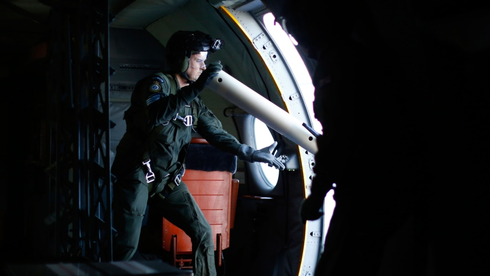 Crewmember Sean Donaldson launches a GPS marker buoy out of a Royal New Zealand Air Force P-3K2 Orion aircraft searching for the missing Malaysian Airlines flight 370 over the southern Indian Ocean, March 29, 2014. (AP / Jason Reed)