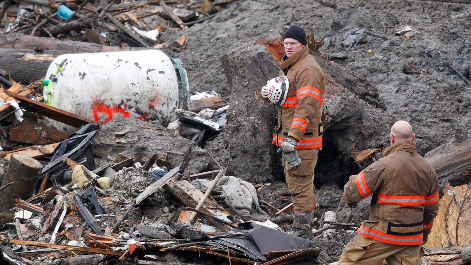 Searchers pause for a moment of silence at the scene of a deadly mudslide Saturday, March 29, 2014, in Oso, Wash. (AP / Elaine Thompson, Pool)