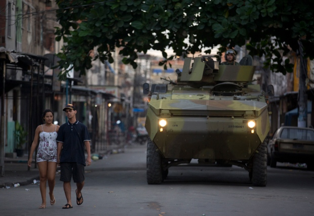 A couple walk pass a Navy armored in a Rio slum