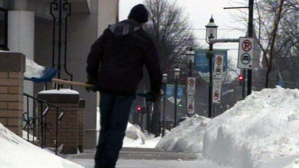 A man shovels a sidewalk in Fredericton, N.B., Sunday, March 30, 2014.