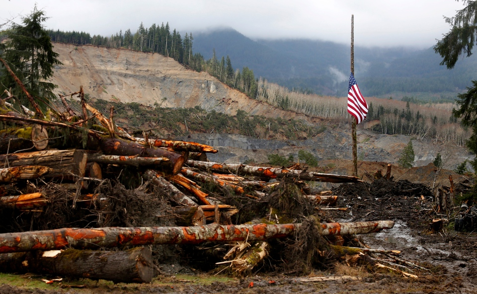 A large American flag hangs at half mast from a post at the mudslide site near Oso, Wash., Sunday, March 30, 2014. (AP  / The Herald, Annie Mulligan)