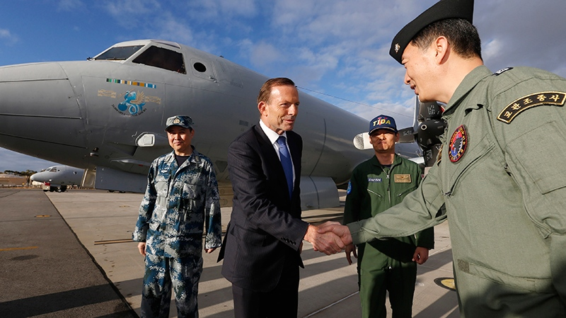 Australian Prime Minister Tony Abbott, left, greets South Korean Navy Captain Lee Jin-young, right, alongside China's Air Force Senior Colonel Liu Dian Jun, left, and Japan's Maritime Self Defence Force Commander Hidetsugu Iwamasa in front of a Royal Australian Air Force AP-3C Orion aircraft at RAAF Base Pearce near Perth, Monday, March 31, 2014. (AP Photo/Jason Reed, Pool)